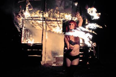 Sasha the Fire Gypsy Massachusettes Fire Performer Fire Fans Dancer Burning Tiki Bar Building